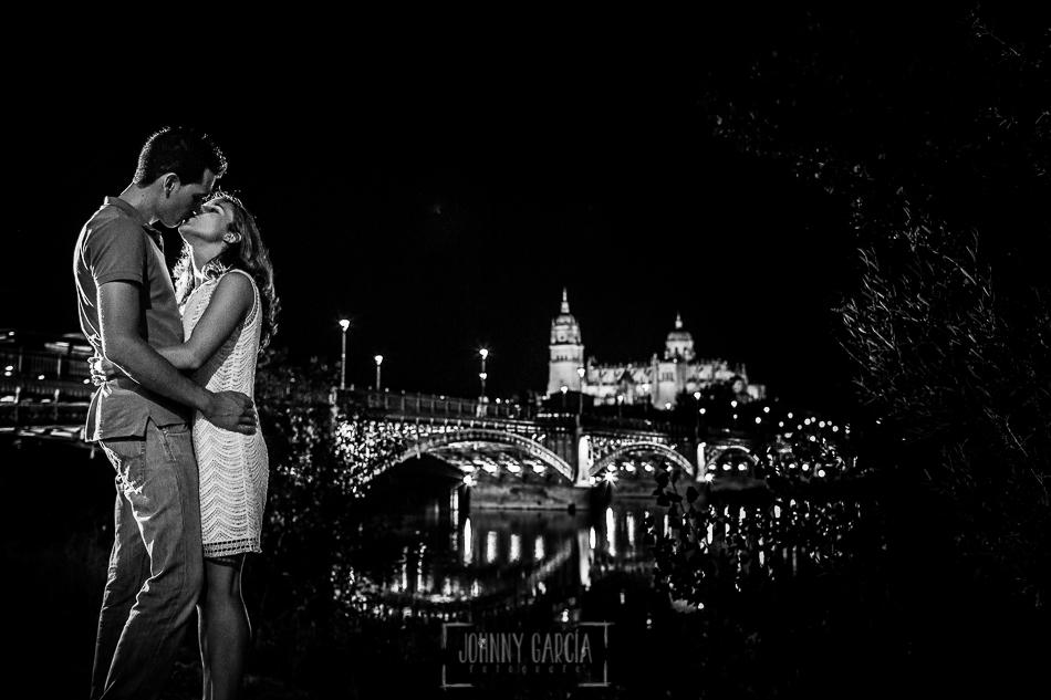Pre boda en Salamanca, Cristina y Santiago se besan, al fondo un puente de Salamanca