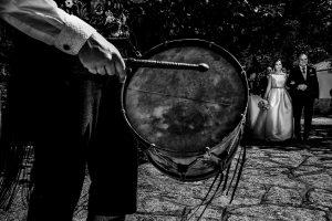 Boda en Hervás, Cáceres, Johnny García, fotógrafo de bodas en Extremadura, Ester y Juan Luis , 2015, Ester espera a la entrada de la Ermita del brazo de su padre, la escena la anima un tamborilero tocando canciones populares
