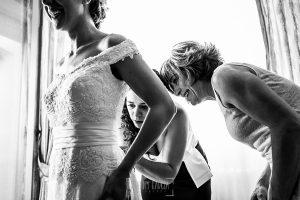 La madre y una amiga de Cristina le ponen los botones al vestido de novia