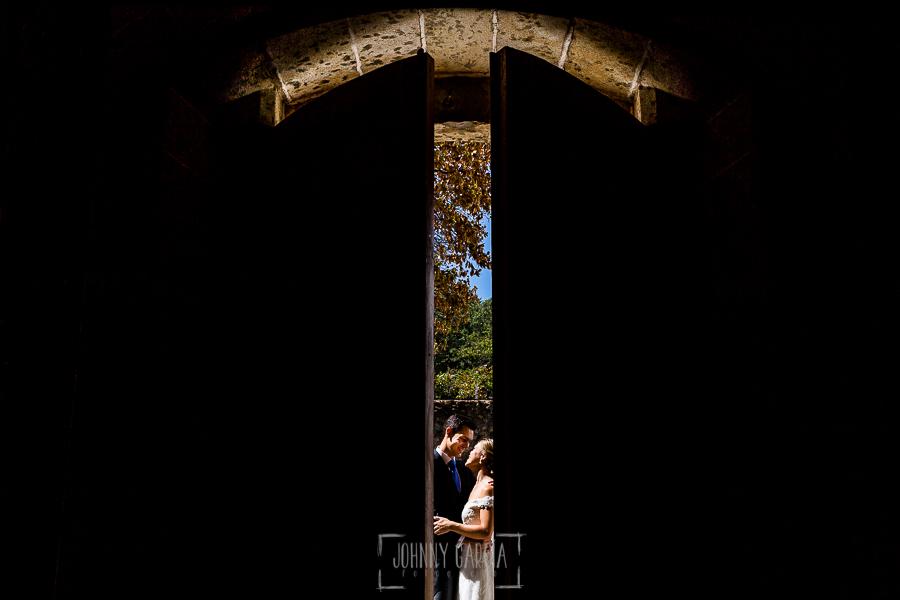 Boda en Béjar de Cristina y Santiago realizada por Johnny Garcia, la pareja vista a través de una rendija de la puerta de la iglesia del Castañar