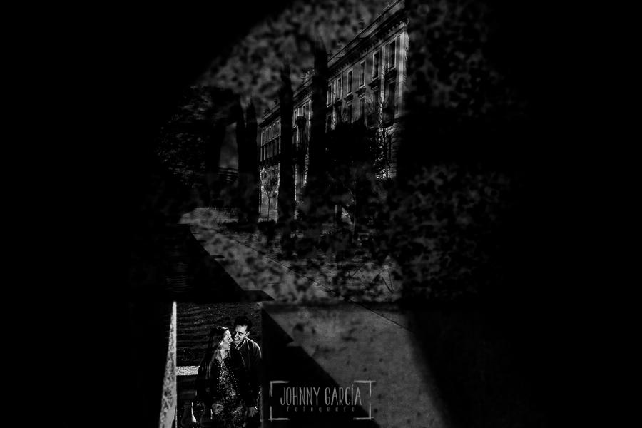 Pre boda en Boadilla del Monte de Laura y Manuel realizada por el fotógrafo de bodas en España Johnny Garcia, fotografía del reflejo de Laura y Manu se abrazan y ríen, el palacio del infante Don Luis all fondo