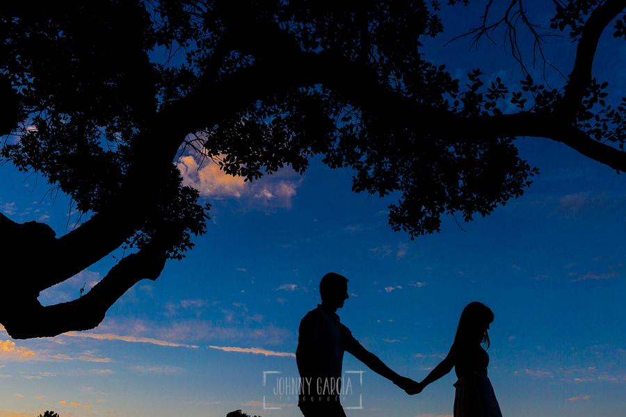 Pre boda en Mohedas de Granadilla de Esmeralda y Luis Miguel realizada por el fotógrafo de bodas en España Johnny Garcia en 2016, Esmeralda y Miguel a contraluz mientras pasean entre encinas por una dehesa extremeña