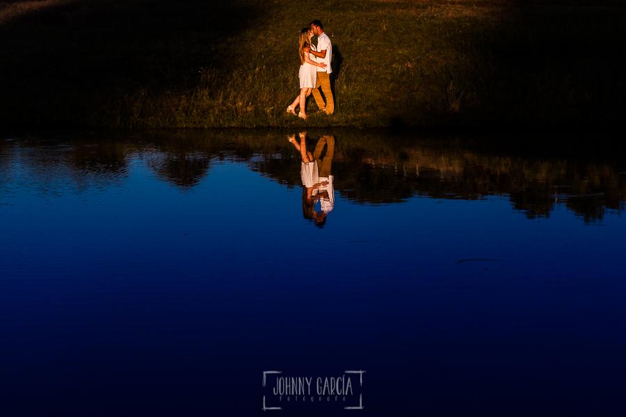 Pre boda en Mohedas de Granadilla de Esmeralda y Luis Miguel realizada por el fotógrafo de bodas en España Johnny Garcia en 2016, Esmeralda y Luis Miguel abrazados y reflejados en una charca de la dehesa extremeña