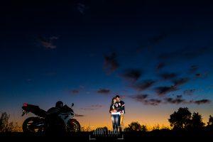 Pre boda en Mohedas de Granadilla de Esmeralda y Luis Miguel realizada por el fotógrafo de bodas en España Johnny Garcia en 2016, Esmeralda y Luis Miguel junto a su moto y un cielo lleno de color tras la puesta de sol