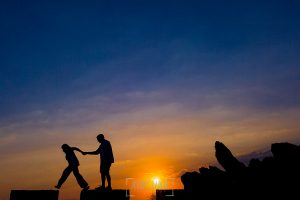 Pre boda en Cáceres de María e Iván realizada por el fotógrafo de bodas en España Johnny Garcia, la pareja anda sobre unas piedra en la puesta de sol