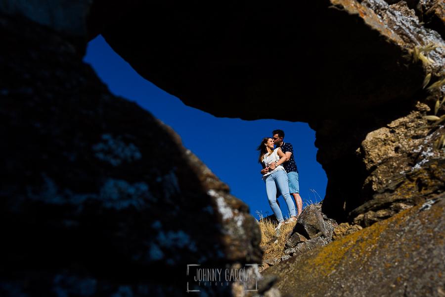 Pre boda Salmantina de Laura y Jonatan realizada por el fotógrafo de bodas en España Johnny García en Salvatierra de Tormes y en Salamanca, Laura y Jonatan abrazados vistos por el hueco de una piedra