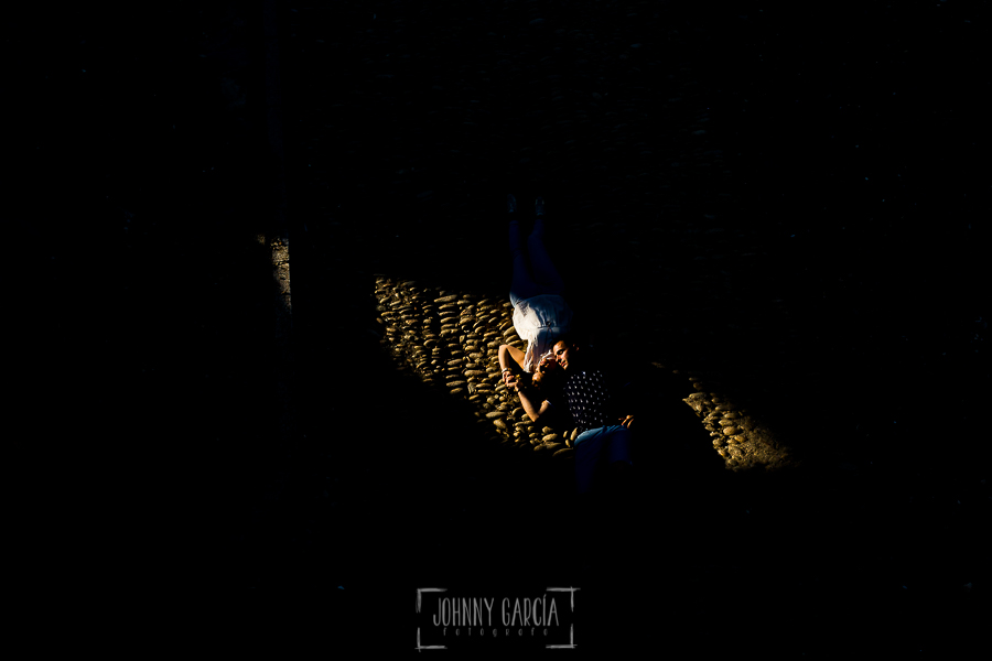 Pre boda Salmantina de Laura y Jonatan realizada por el fotógrafo de bodas en España Johnny García en Salvatierra de Tormes y en Salamanca, la pareja tirados en un suelo empedrado iluminados por un haz de luz