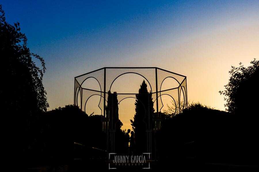Pre boda en Madrid de Marta y Mauricio realizada por Johnny Garcia, fotógrafo de bodas en España, en 2016 la silueta de la pareja debajo de un cenador del parque Juan Carlos I