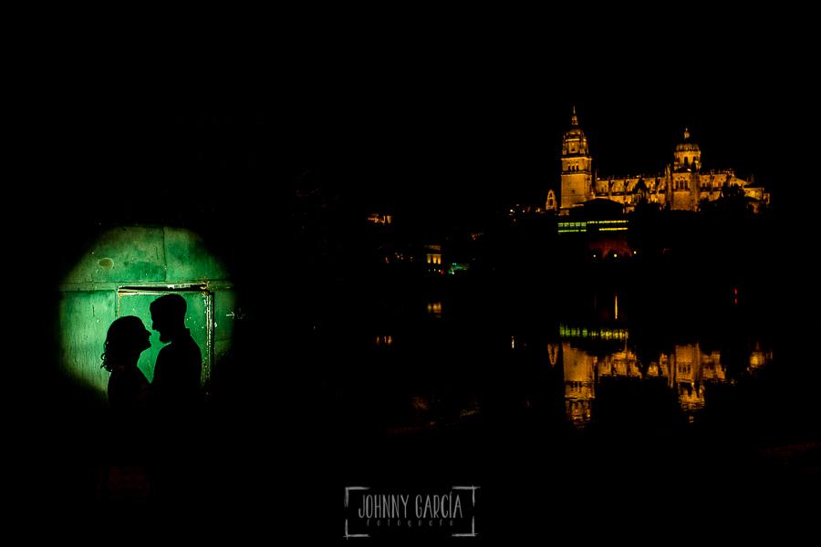 pre boda en Salamanca de Beatriz y Jose Manuel realizada por el fotógrafo de bodas en Salamanca Johnny Garcia, la pareja a contraluz sobre una caseta del embarcadero del río Tormes en Salamanca, al fondo la catedral reflejada en el río
