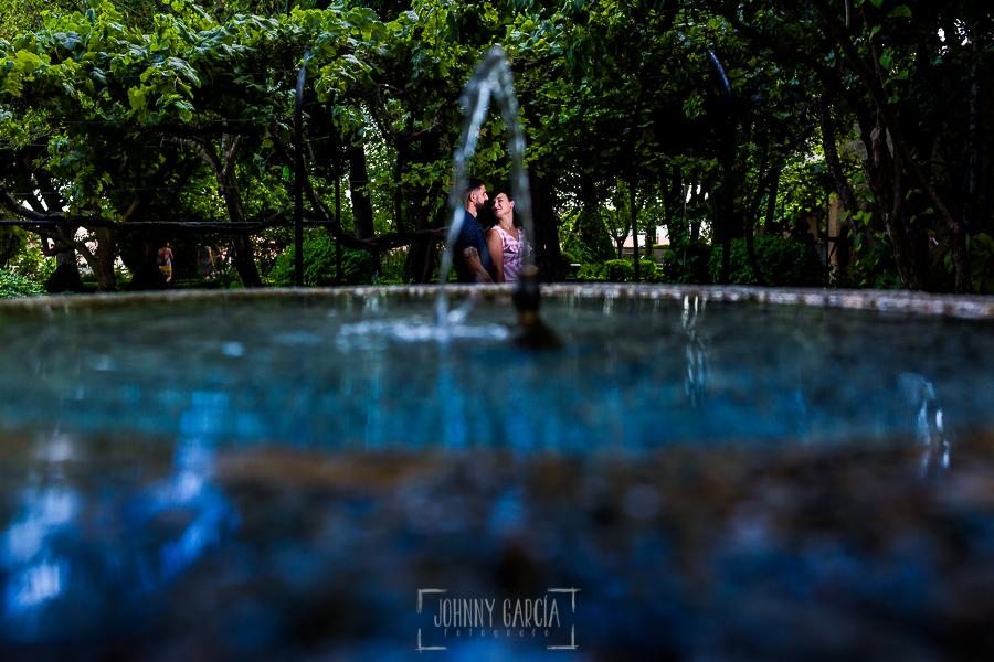 pre boda en Salamanca de Beatriz y Jose Manuel realizada por el fotógrafo de bodas en Salamanca Johnny Garcia, la pareja vista a través del chorro de agua de la fuente del parque de Calixto y Melibea