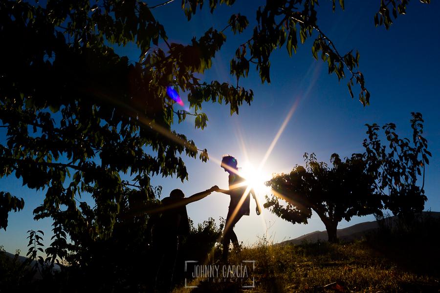 Fotografía de la pre boda en Tornavacas de Mercedes y Fran, realizada por Johnny García, fotógrafo de bodas en Extremadura, Merecedes baja un bancal ayudada por Fran a contraluz