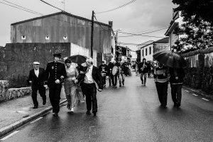 Boda de Noelia y César en Horcajo de Montemayor realizada por Johnny García, Fotógrafo de bodas en Salamanca, César sale junto a los invitados hacia la iglesia mientras llueve