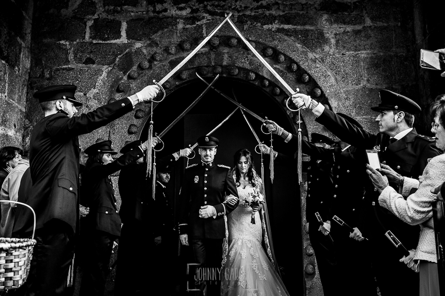 Boda de Noelia y César en Horcajo de Montemayor realizada por Johnny García, Fotógrafo de bodas en Salamanca, los novios salen de la iglesia y los compañeros de César levantan las espadas