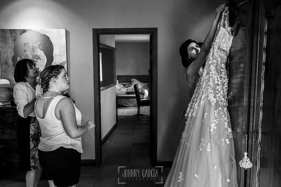 Boda en la Hacienda Zorita de Salamanca de Emma y Michael realizada por Johnny García, wedding photographers in Spain, una dama coge el vestido de Emma