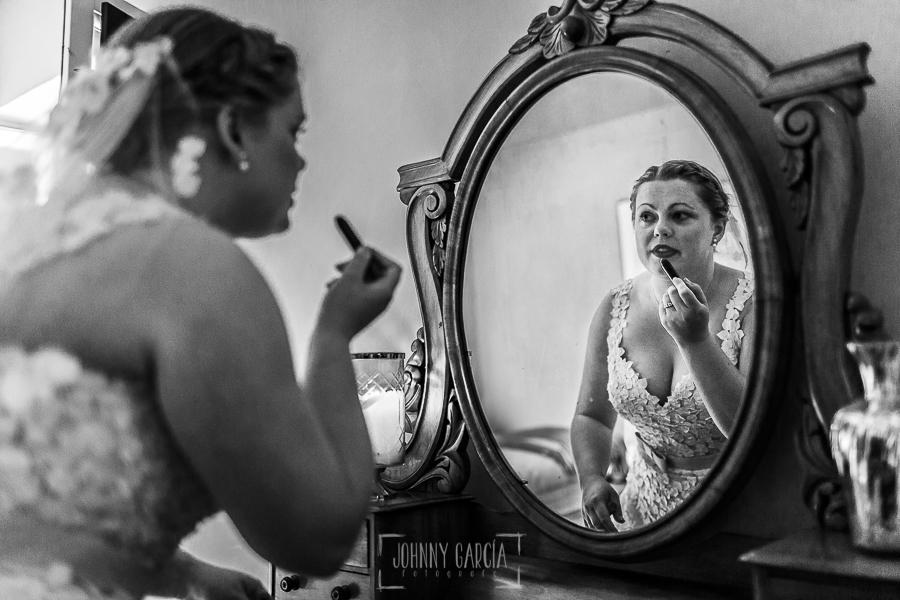 Boda en la Hacienda Zorita de Salamanca de Emma y Michael realizada por Johnny García, wedding photographers in Spain, Emma se retoca los labios delante de un espejo