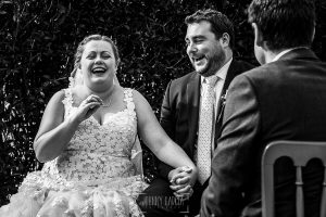 Boda en la Hacienda Zorita de Salamanca de Emma y Michael realizada por Johnny García, wedding photographers in Spain, la pareja rie en un momento de la ceremonia