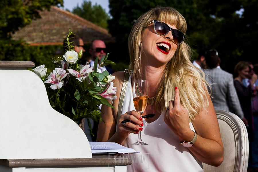 Boda en la Hacienda Zorita de Salamanca de Emma y Michael realizada por Johnny García, wedding photographers in Spain, una invitada rie mientras firma