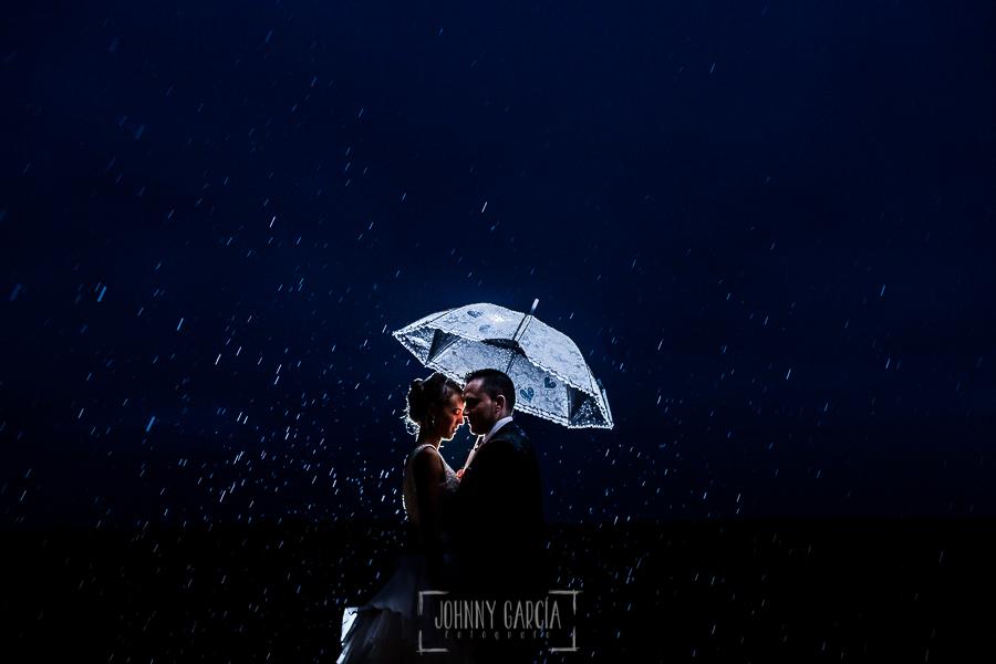 Boda en Salamanca de Laura y Manu, realizada por el fotógrafo de bodas en Salamanca Johnny García, Laura y Manu se refujian de la lluvia bajo un paraguas