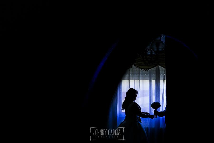 Boda en Guijuelo, Salamanca, de María Eugenia y David, realizada por Johnny García, fotógrafo de bodas en Salamanca, María Eugenia a contraluz con su padre entregándole el ramo de flores