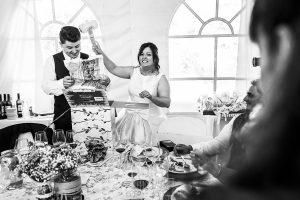 Boda en Guijuelo, Salamanca, de María Eugenia y David, realizada por Johnny García, fotógrafo de bodas en Salamanca, María Eugenia da con un martillo de plástico que le han regalado los amigos