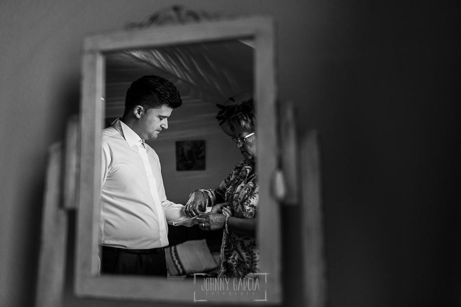 Boda en Guijuelo, Salamanca, de María Eugenia y David, realizada por Johnny García, fotógrafo de bodas en Salamanca, la madre de David le ayuda a vestirse
