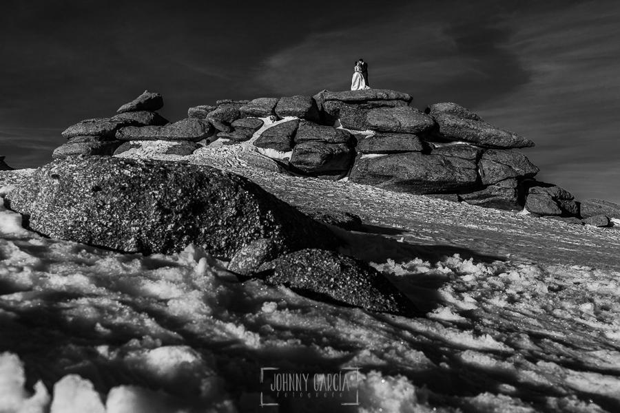 Boda en Guijuelo, Salamanca, de María Eugenia y David, realizada por Johnny García, fotógrafo de bodas en Salamanca, María Eugenia y David subidos en una montaña de piedras rodeados por la nieve