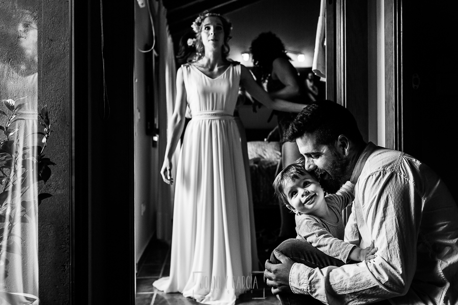 Boda en Hervás y postboda en Trevejo de Sofía y Charly realizada por Johnny García, fotógrafo de bodas en Extremadura, Charly con el pequeño de la familia, al fondo Sofía mientras se viste