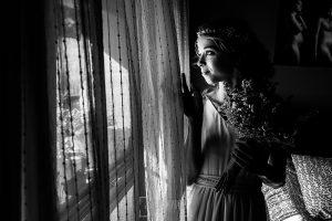 Boda en Hervás y postboda en Trevejo de Sofía y Charly realizada por Johnny García, fotógrafo de bodas en Extremadura, Sofía mira a los invitados por la ventana
