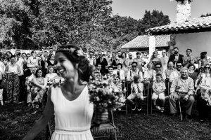 Boda en Hervás y postboda en Trevejo de Sofía y Charly realizada por Johnny García, fotógrafo de bodas en Extremadura, la novia sonríe, al fondo los invitados