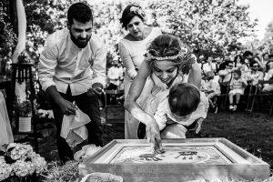 Boda en Hervás y postboda en Trevejo de Sofía y Charly realizada por Johnny García, fotógrafo de bodas en Extremadura, los novios junto a su hijo plasman sus manos en un cuadro