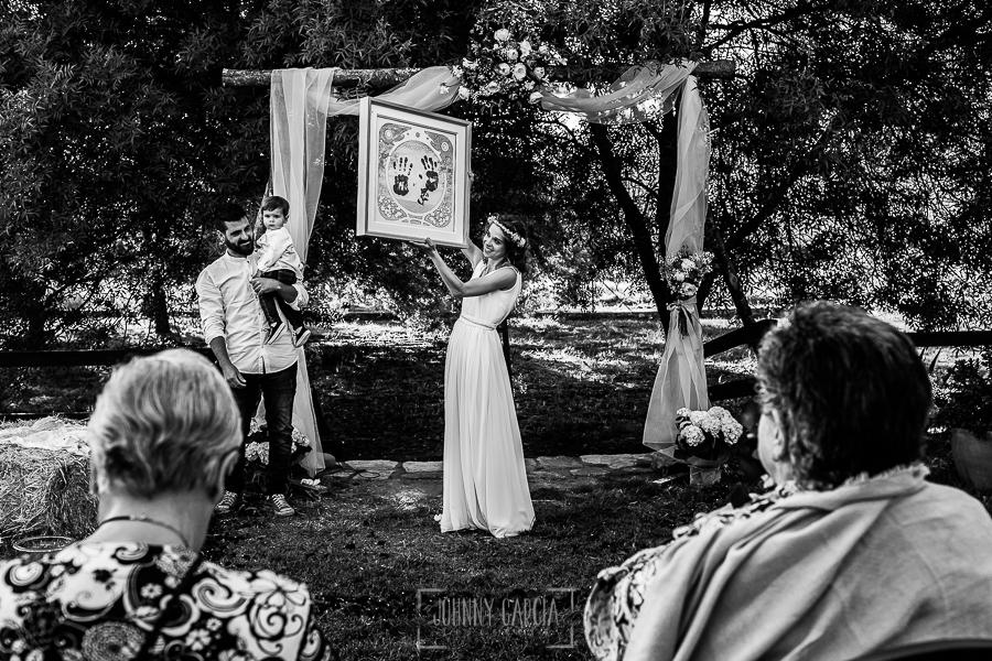 Boda en Hervás y postboda en Trevejo de Sofía y Charly realizada por Johnny García, fotógrafo de bodas en Extremadura, Sofía enseña un cuadro que han realizado para la boda