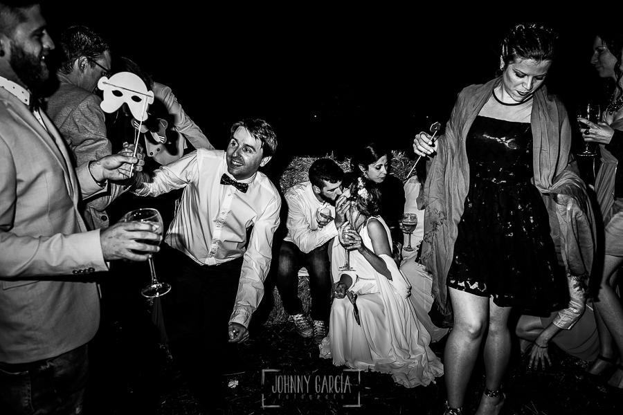 Boda en Hervás y postboda en Trevejo de Sofía y Charly realizada por Johnny García, fotógrafo de bodas en Extremadura, los novios se besan rodeados de amigos