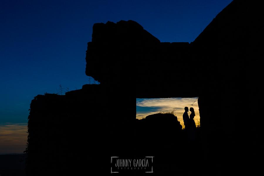 Boda en Hervás y postboda en Trevejo de Sofía y Charly realizada por Johnny García, fotógrafo de bodas en Extremadura, un contraluz con la silueta de los novios en una de las entradas al castillo de Trevejo