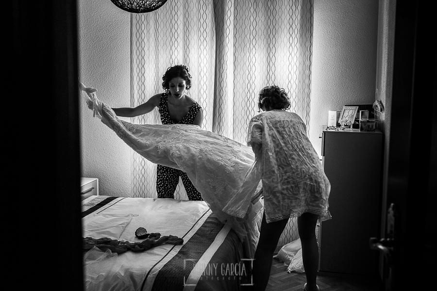 Post boda en Llanes y boda en Medinilla de Laura y Jonatan realizada por Johnny Garcia, fotografo de bodas en Asturias, Laura y su hermana descuelgan el vestido de novia