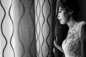 Post boda en Llanes y boda en Medinilla de Laura y Jonatan realizada por Johnny Garcia, fotografo de bodas en Asturias, Laura mira por la ventana
