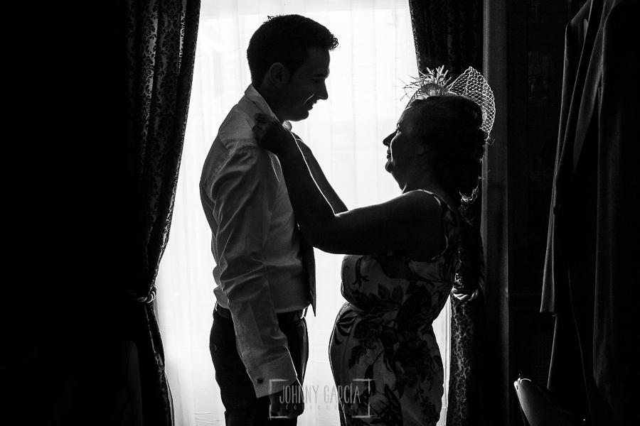 Post boda en Llanes y boda en Medinilla de Laura y Jonatan realizada por Johnny Garcia, fotografo de bodas en Asturias, la madre de Jonatan le ayuda a vestirse