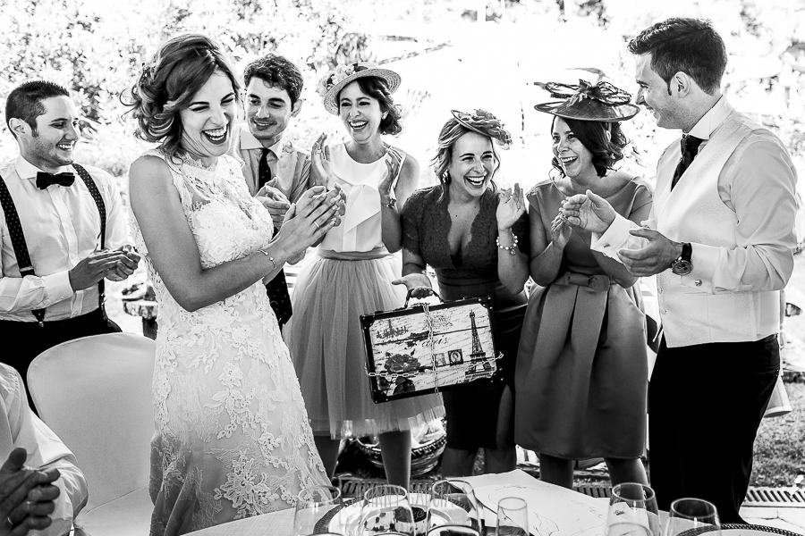 Post boda en Llanes y boda en Medinilla de Laura y Jonatan realizada por Johnny Garcia, fotografo de bodas en Asturias, los amigos de los novios le llevan unos regalos a la mesa presidencial