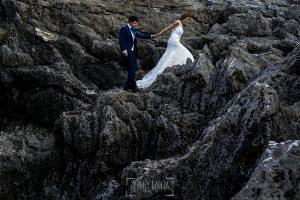 Post boda en Llanes y boda en Medinilla de Laura y Jonatan realizada por Johnny Garcia, fotografo de bodas en Asturias, la pareja suben por un acantilado