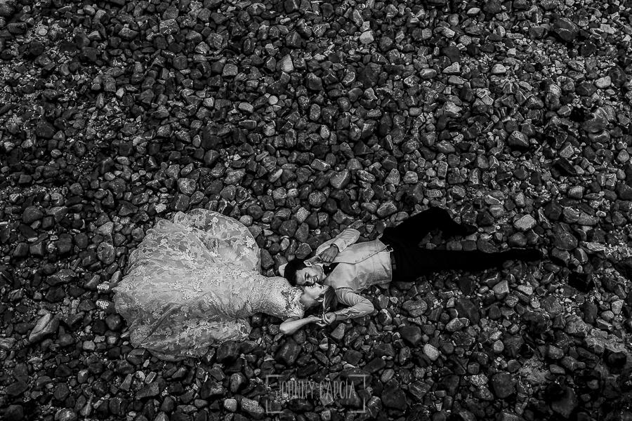 Post boda en Llanes y boda en Medinilla de Laura y Jonatan realizada por Johnny Garcia, fotografo de bodas en Asturias, retrato de Laura y Jonatan en una playa de piedras