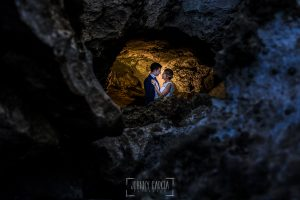Post boda en Llanes y boda en Medinilla de Laura y Jonatan realizada por Johnny Garcia, fotografo de bodas en Asturias, la pareja en un recoveco de piedras en una playa de Llanes