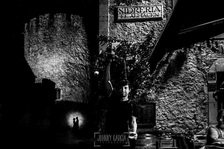 Post boda en Llanes y boda en Medinilla de Laura y Jonatan realizada por Johnny Garcia, fotografo de bodas en Asturias, la pareja al fondo, en primer plano una sidrería típica de Llanes