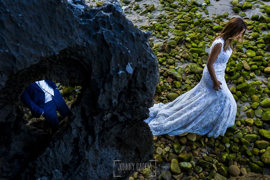 Post boda en Llanes y boda en Medinilla de Laura y Jonatan realizada por Johnny Garcia, fotografo de bodas en Asturias, Laura pasea por unas rocas al lado del mar