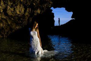Post boda en Llanes y boda en Medinilla de Laura y Jonatan realizada por Johnny Garcia, fotografo de bodas en Asturias, retrato de Laura dentro del agua del mar, al fondo Jonatan