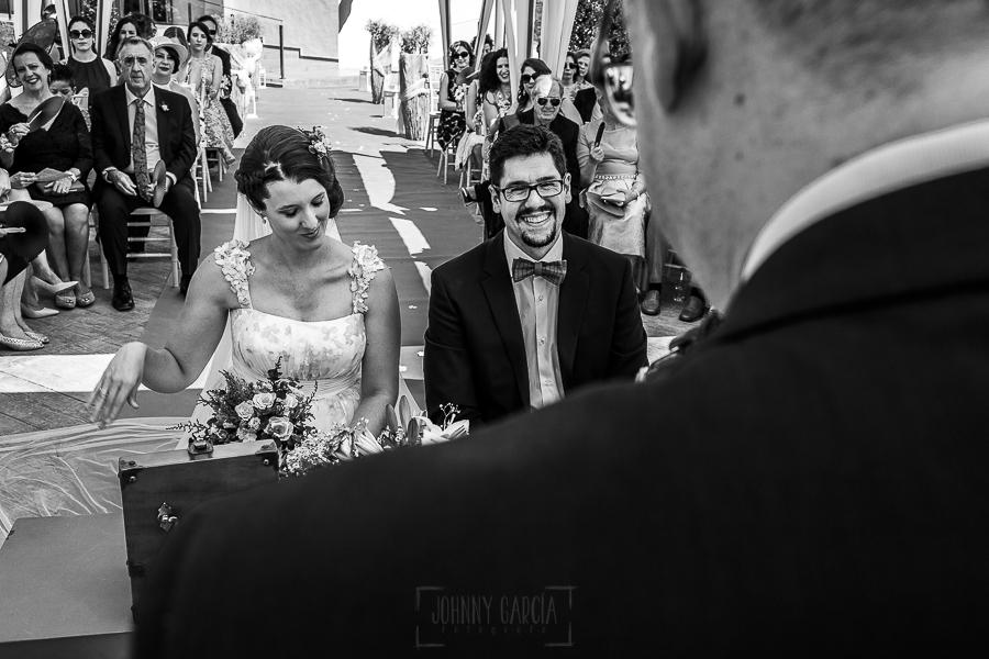 Boda en Granada de Marta y Mauricio realizada por Johnny García, fotógrafo de bodas en Granada, la pareja ríe con las palabras del oficiante de la ceremonia