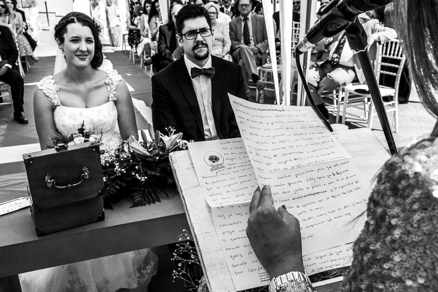 Boda en Granada de Marta y Mauricio realizada por Johnny García, fotógrafo de bodas en Granada, la pareja atenta a las palabras que les dirige la hermana de Mauricio