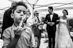 Boda en Granada de Marta y Mauricio realizada por Johnny García, fotógrafo de bodas en Granada, uno de los peques juega con un pompero mientras los novios salen del lugar de la ceremonia