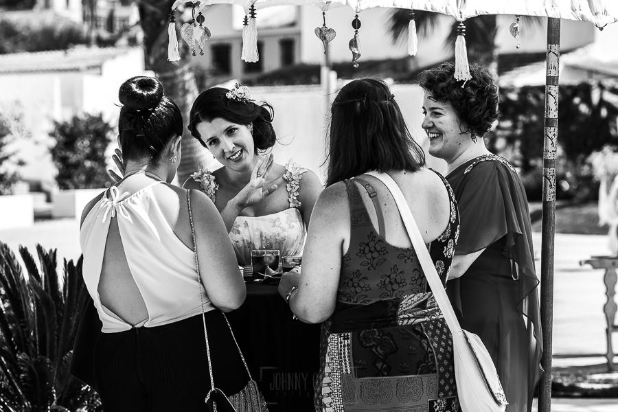 Boda en Granada de Marta y Mauricio realizada por Johnny García, fotógrafo de bodas en Granada, Marta hablando con amigas durante el aperitivo