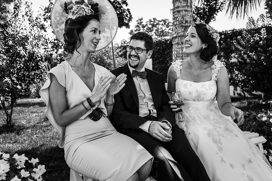 Boda en Granada de Marta y Mauricio realizada por Johnny García, fotógrafo de bodas en Granada, la pareja hablando y riendo con la hermana de Marta