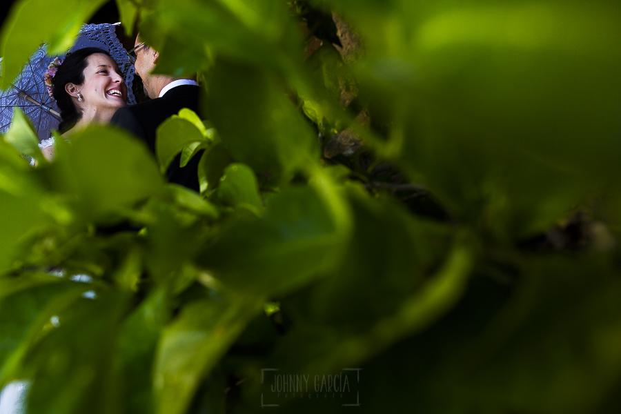 Boda en Granada de Marta y Mauricio realizada por Johnny García, fotógrafo de bodas en Granada, un retrato de la pareja por el hueco de las hojas de un naranjo de la Alhambra