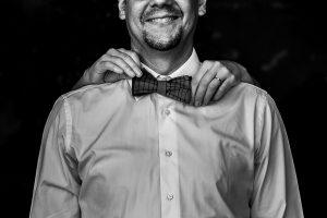 Boda en Granada de Marta y Mauricio realizada por Johnny García, fotógrafo de bodas en Granada, un retrato de Mauricio mientras le colocan la pajarita de Spiderman
